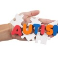 The word AUTISM spelled out over blank puzzle in a hand.